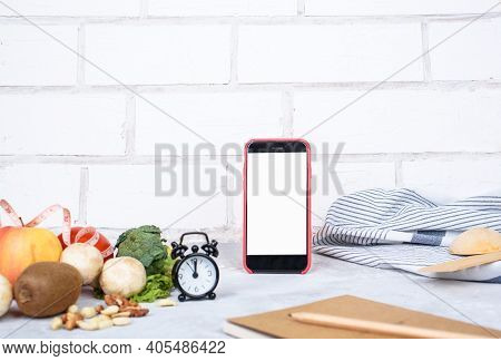 Phone With White Mockup, Little Clock, And Different Kitchen And Cooking Utensils On Light Table. Cu