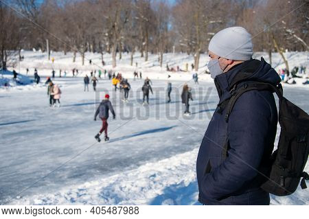 Man Wearing Protection Mask During Covid-19 Pandemic Looking At Ice Skaters