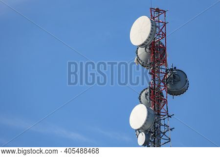 The Upper Portion Of A Communications Tower Holds An Array Of Several Microwave Backhaul Antennas Wi