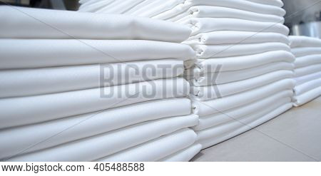 Stacks Of Folded White Fabrics Or Sheets In A Laundry. Cleaning Service For Institutions And Industr