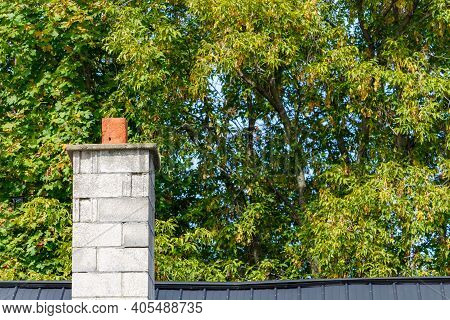A Chimney On The Metal Roof Of A House Stands In Front Of Leafy Green Trees Just Beginning To Turn T