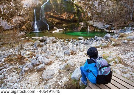 Young Man In Bright Blue Sportive Jacket Relaxing Near Waterfall. Early Spring, Slovenia. Mental Hea