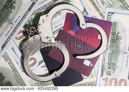Steel Handcuffs And Credit Cards Lying On The Background Of American Dollars. Dollar And Credit Card