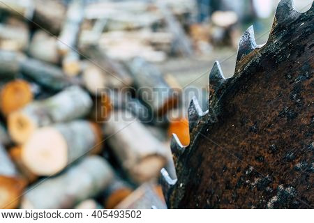 Out Of Focus Pile Of Logs And Saw - Abstract Concept Of Spring Chores With Copy Space
