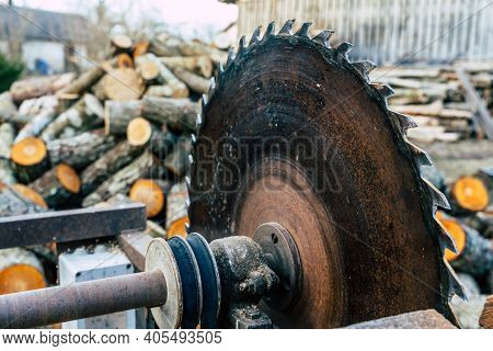 Circular Saw With Alder Log Pile In Background With Copy Space, Concept Of Hard Work