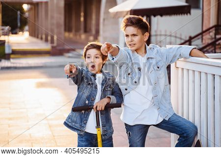 Two Attractive Teenagers Of Caucasian Nationality 7 And 9 Years Old Standing On Sunny Evening Street