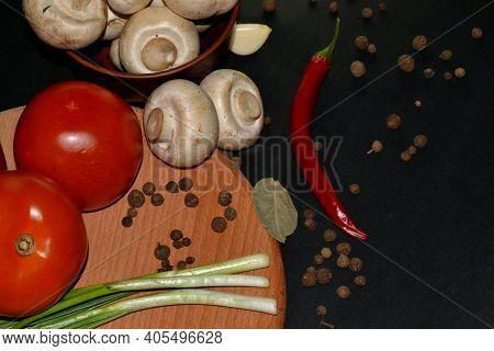 Close Up Of Fresh Mushroom, Red Hot Pepper, Tomato, Garlic, Bay Leaf And Allspice. Dark Background