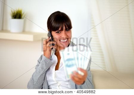 Smiling Woman Speaking On Cellphone With Money