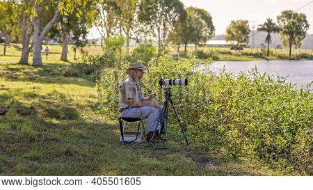Mackay, Queensland, Australia - January 2021: Male Retiree Photographer Taking Photos Of Birds On A