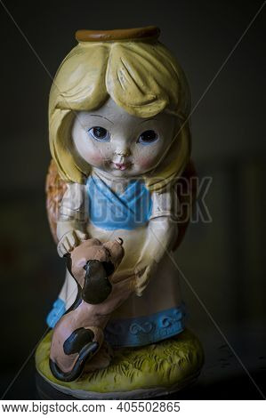 A Ceramic Figurine Of A Little Girl Affectionately Stroking Her Puppy
