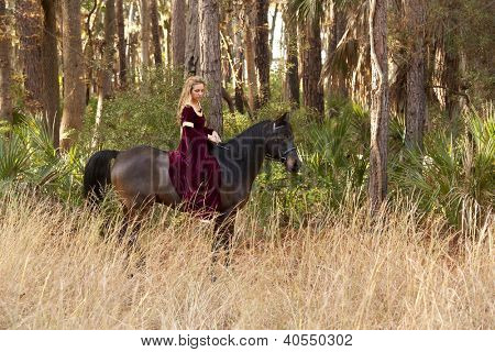 woman in medieval dress riding bareback through forest