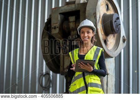 Young Female In Protective Uniform Inspecting Industrial Machine And Taking Necessary Notes On Digit