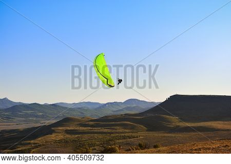 A Green Paraglider Flies Over The Mountains Against The Blue Sky