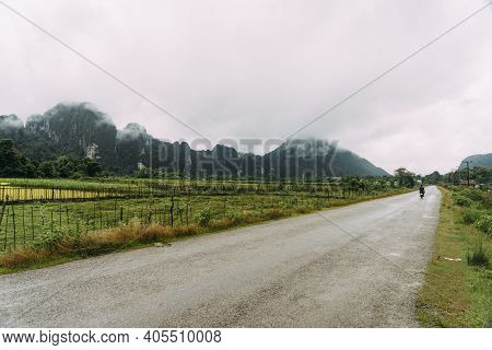 Motorcycle Driving On Back Road In Vang Vieng, Laos, With Mountains And Green Rice Fields In The Rai