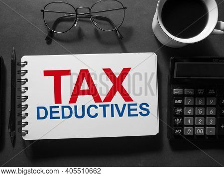Tax Deductives, Text Words Typography Written On Book Against Dark Background, Life And Business Mot