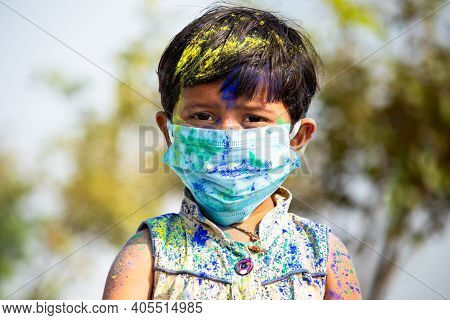 Portrait Of Young Cute Little Girl Kid With Medical Face Mask With Applied Holi Powder Looking At Ca