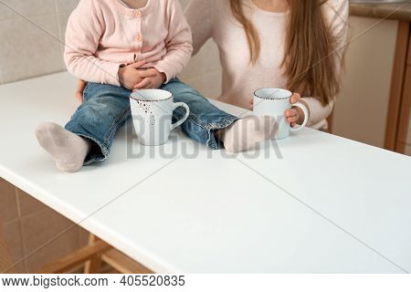 Big White Cups In Female And Baby Hands. Breakfast In Family, Details.