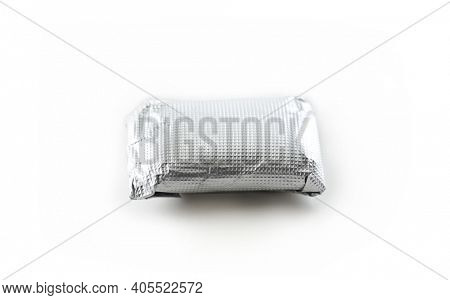 Tablet of gum or candy, wrapped in tin foil or aluminum foil, isolated on white.