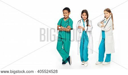 Group Of Positive Multiethnic Kids Wearing Medical Uniforms, Full-length. Concept Of Future Doctors