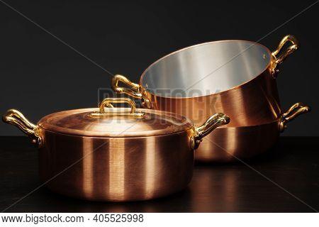 Set Of Copper Cookware Over Dark Background