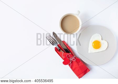A Cup Of Coffee, A Plate With A Fried Egg In The Form Of A Heart And Cutlery In A Red Napkin With De