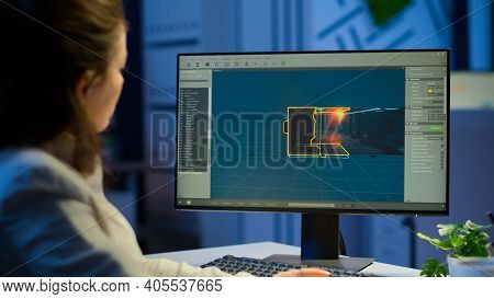 Young Woman Game Designer Looking At Computer Screen Working At Project Studio Office Late At Night.