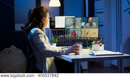 Employee Working Overtime From Business Office Late At Night Discussing With Partners Online Using W