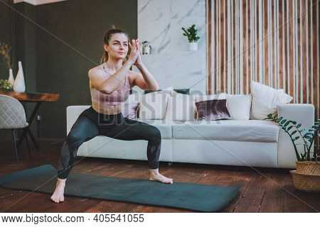 Young Fit Woman In Sportswear Do Squat Exercise Indoors In Living Room. Online Indoors Workout. Trai