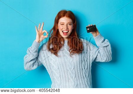 Happy Redhead Girl In Sweater Showing Credit Card And Okay Sign, Recommending Bank Offer, Standing O