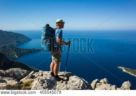 Hiking on Lycian way. Man with backpack standing on rock cliff high above Mediterranean sea enjoying the view, Trekking in Turkey on Lycian Way trail, outdoor activity