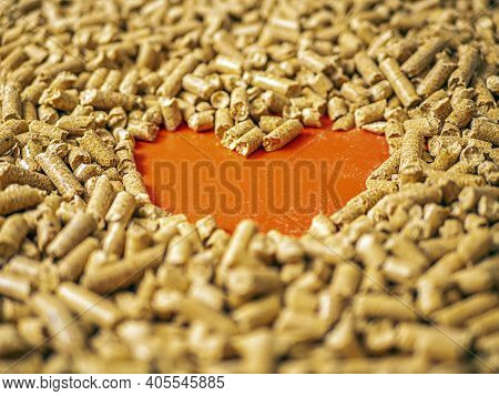 Natural Wooden Pellets Background And Empty Hole As Red Heart. Close-up Wood Pellet Pattern.