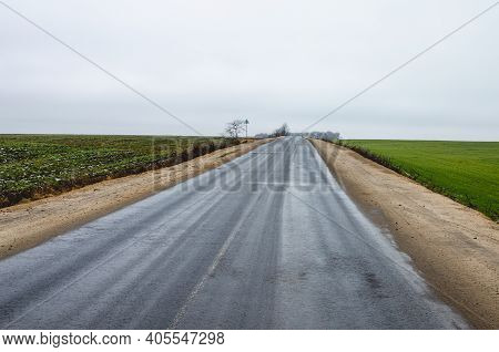 Gray Cloudy Landscape, View Of An Empty Asphalt Road Without Cars And People. Winter Without Snow Du