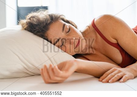 Beautiful girl sleeping in her bed and relaxing in the morning. Young woman sleeping under white blanket in her bed at home. Beauty sleepy girl lying in a comfortable bed with closed eyes.