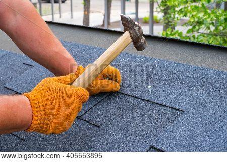 Worker Hands Installing Bitumen Roof Shingles Using Hammer In Nails.
