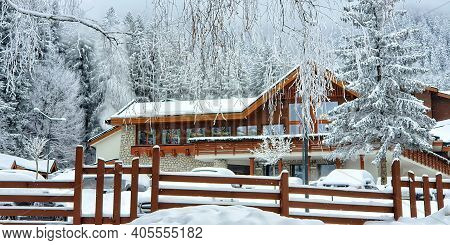 Large Snow Covered Wooden House In The Mountains. Snowy Fairytale Winter Landscape. Villa In A Fir F