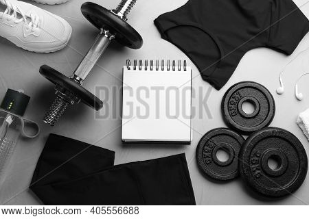Flat Lay Composition With Sportswear, Notebook And Equipment On Grey Table. Gym Workout Plan