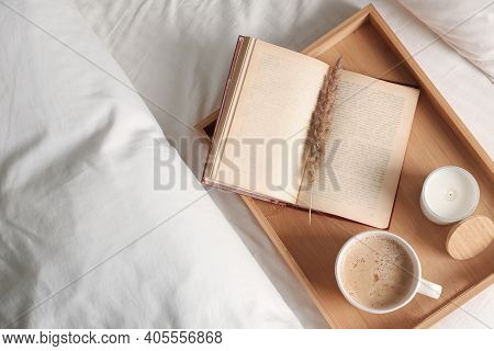 Cup Of Aromatic Coffee, Book And Candle On Bed With Soft Blanket Indoors, Top View