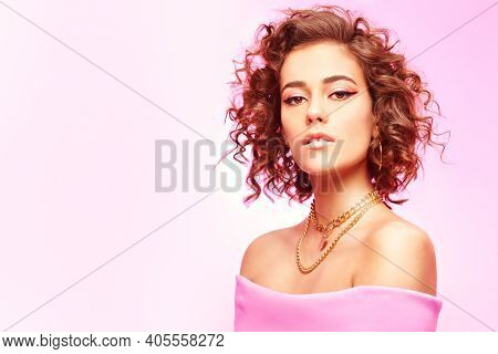 Beauty and jewelry concept. Portrait of a gorgeous tanned girl posing in golden jewelry on a gentle pink background. Make-up and hairstyle. Copy space.