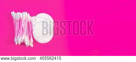 White Cotton Cotton Pads And Pink Cotton Swabs On A Pink Background. Copy Space.