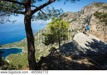 Hiking on Lycian way. Man with backpack looking down from steep rock high above Mediterranean sea, Trekking in Turkey on Lycian Way trail, outdoor activity.