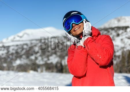 Girl snowboarder in a helmet and mask holds her palms to her face and smiles. Sheregesh resort.