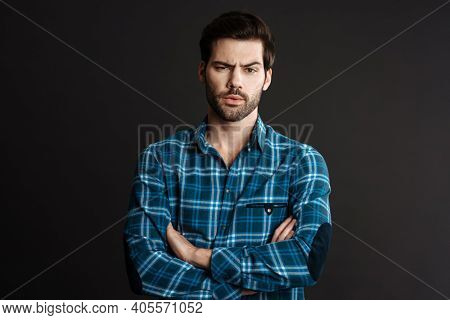 Perplexed handsome unshaven guy posing with arms crossed isolated over black background
