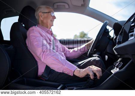 Interior Shot Of Smiling Senior Man Enjoying Driving Car With Hand On Gear Shift