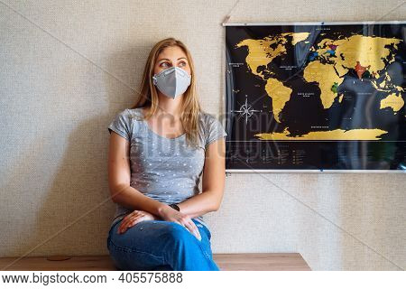Beautiful Girl Stays At Home Because Of Coronovirus, Sitting Near The World Map And Dreaming Of Trav