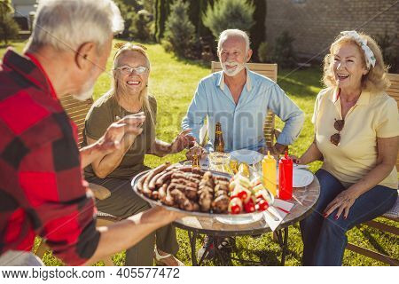 Group Of Cheerful Senior Friends Having An Outdoor Lunch In The Backyard, Gathered Around The Table,