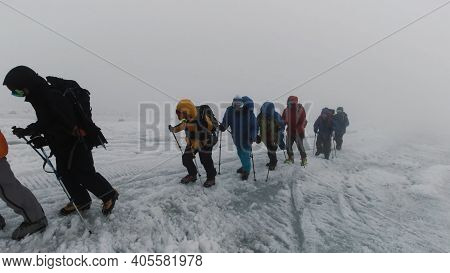 Mountaineering Activity On The Steep Mountain Slope. Clip. Group Of Extreme Tourists Walking One By