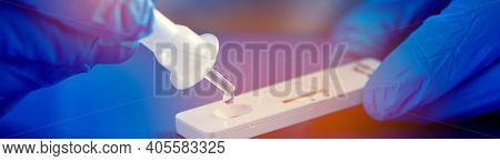 a healthcare worker, wearing blue surgical gloves, places the sample into the covid-19 antigen diagnostic test device, in a panoramic format to use as header or web banner