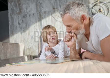 Dad And Child At Home Talking On Bed
