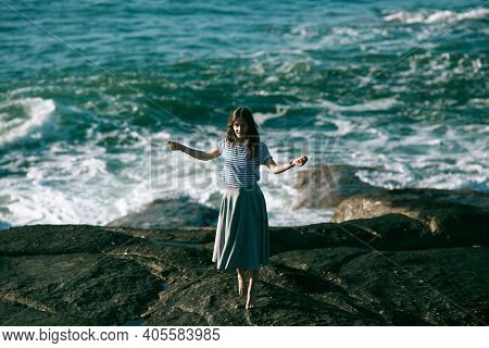The dancer woman is engaged in choreography on rocky Alantic coast.