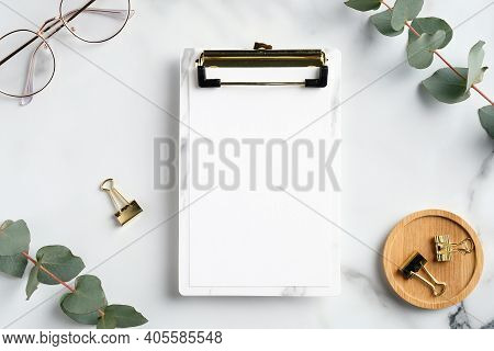 Home Office Workspace With Clipboard Mockup, Glasses, Office Supplies And Eucalyptus Leaves. Flat La